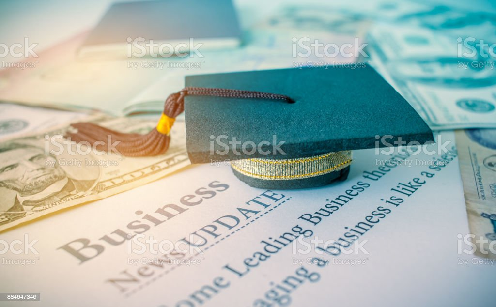 Graduation cap on a letter book, Business News update, Concept of graduate MBA abroad in university, requires a lot foreign currency Dollars to bring success. stock photo