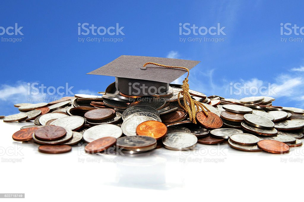 Graduation cap on a pile of coins stock photo