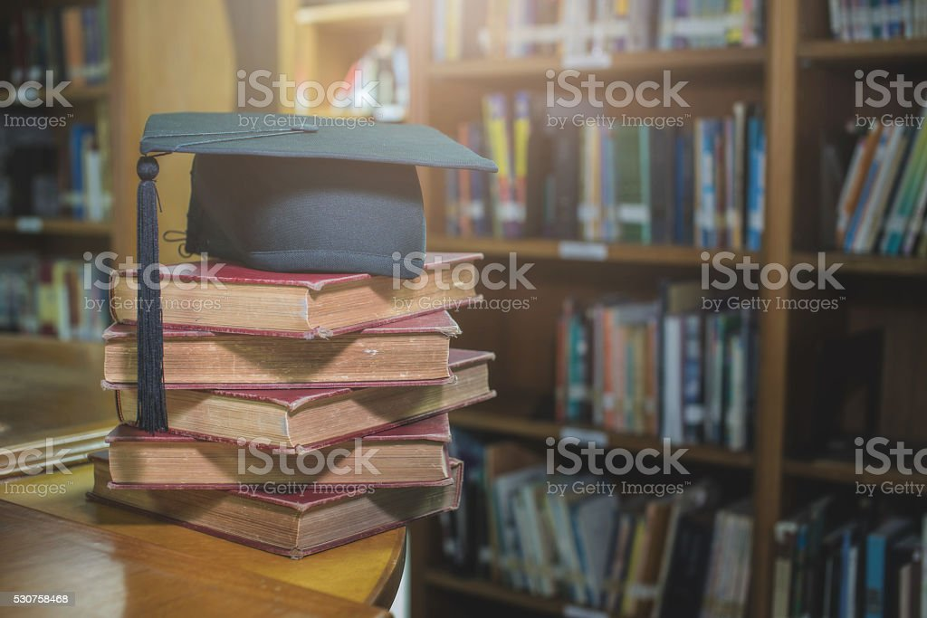 graduation cap on Books step in Library room stock photo
