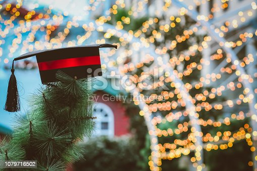 istock Graduation cap on Christmas tree with champion show success in education at yellow light bokeh with copy space for design 1079716502