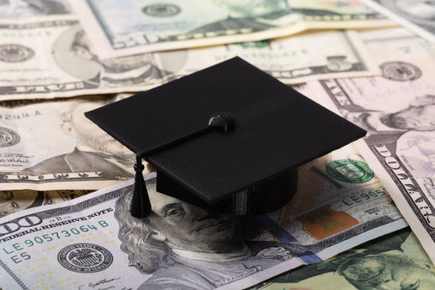 graduation cap on dollar banknotes - scholarship stock pictures, royalty-free photos & images
