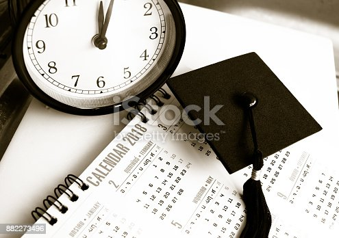 istock Graduation cap on Thai alphabet Calendar 2018 page background with time Clock, Education international Concept, Black and white tone 882273496
