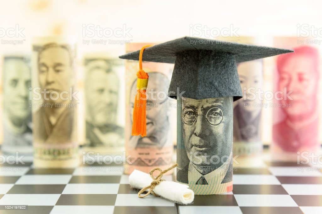 Graduation cap put on AUD 20 dollar bill, a diploma or certificate, famous currencies. Concept of competition on education market which students seek to study at the best and prestigious institution. stock photo