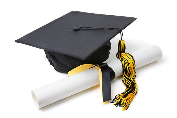 Graduation cap with a tassel and a rolled diploma stock photo