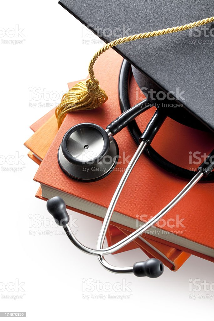 Graduation cap with books and stethoscope stock photo