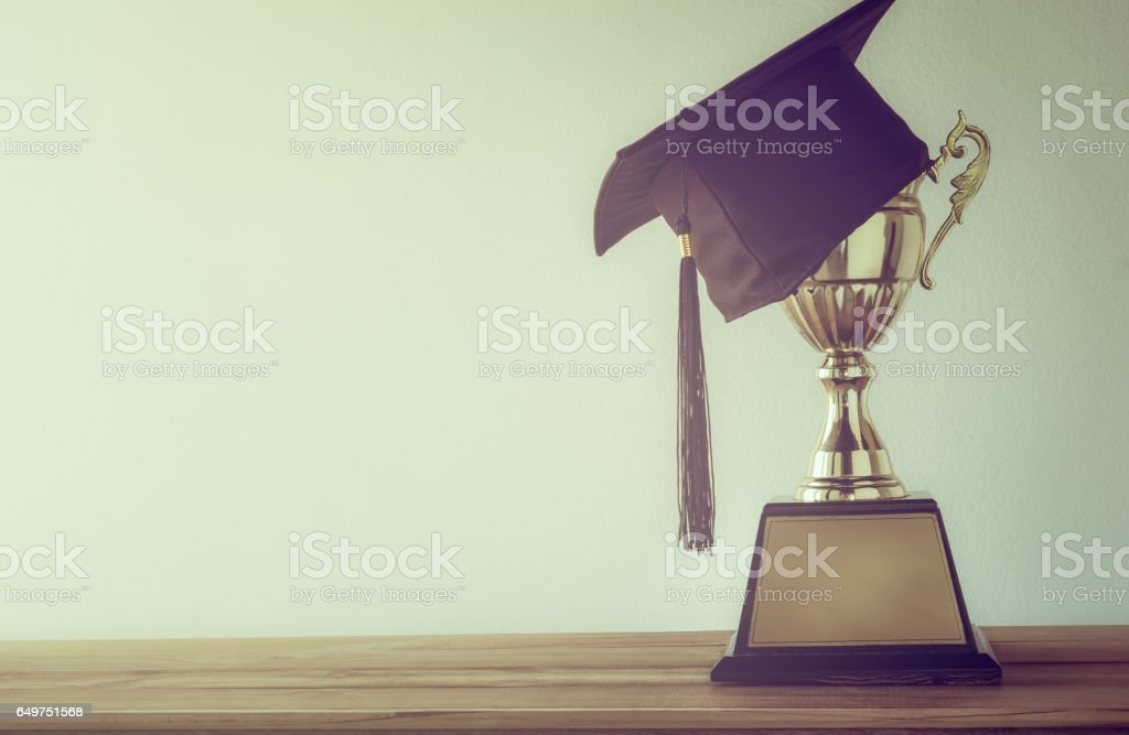 graduation cap with champion golden trophy on wood table with copy space ready for your design.graduation, success, education, concept stock photo