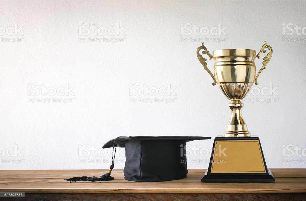 graduation cap with champion golden trophy on wood table with stock photo