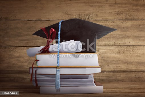 istock Graduation cap with graduation paper on a stack of book 654454466