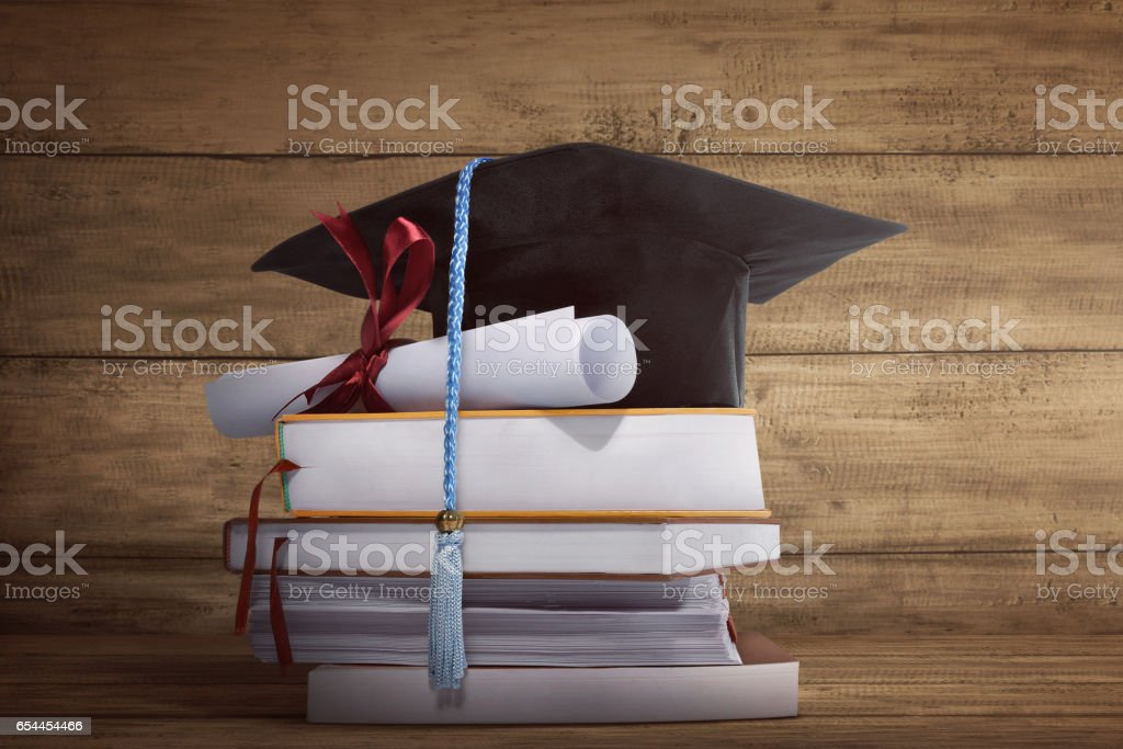 Graduation cap with graduation paper on a stack of book stock photo