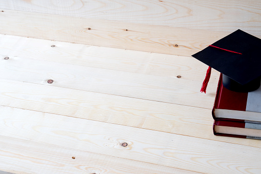 istock Graduation cap with graduation paper on a stack of book 880973538