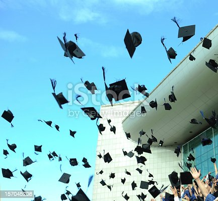 1009462356 istock photo Graduation caps flying through the air 157045208