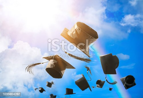 istock Graduation caps, hat thrown in the air with sun ray blue sky abstract background. 1035654262