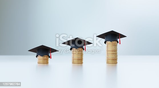 Black graduation caps sitting above coin stacks over white surface in front of defocused background. Horizontal composition with selective focus and copy space. Education and savings concept.