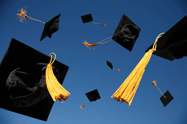 Graduation Caps Thrown in the Air  tassel stock pictures, royalty-free photos & images
