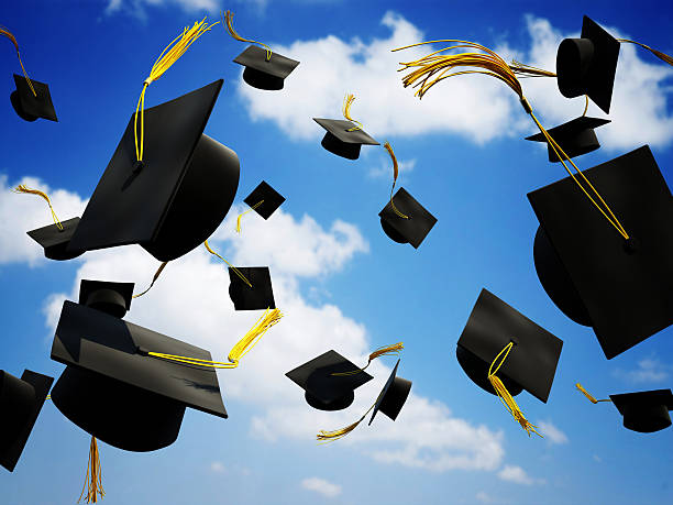 Graduation caps thrown in the air stock photo