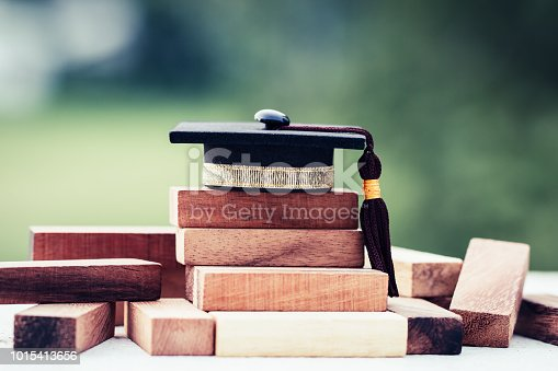 istock Graduation celebrating cap on wooden square blocks tower. Blank space for letter e.g education, study plan, graduate, etc. Ideas for Successive business abroad international Educational 1015413656
