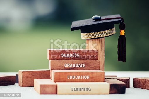 istock Graduation celebrating cap on wooden square blocks tower. Blank space for letter e.g education, success, graduate, etc. Ideas for Successive business abroad international Educational 1015413722