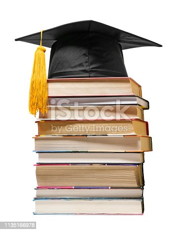 Graduation cap on a stack of books, isolated on a white background.