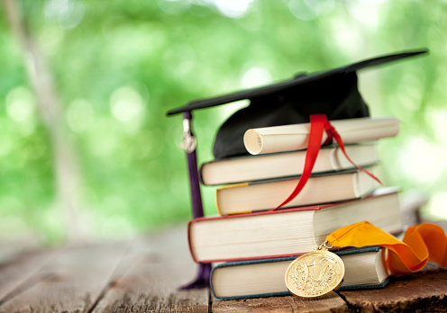 Graduation cap on a stack of books with valedictorian medal of honor and diploma