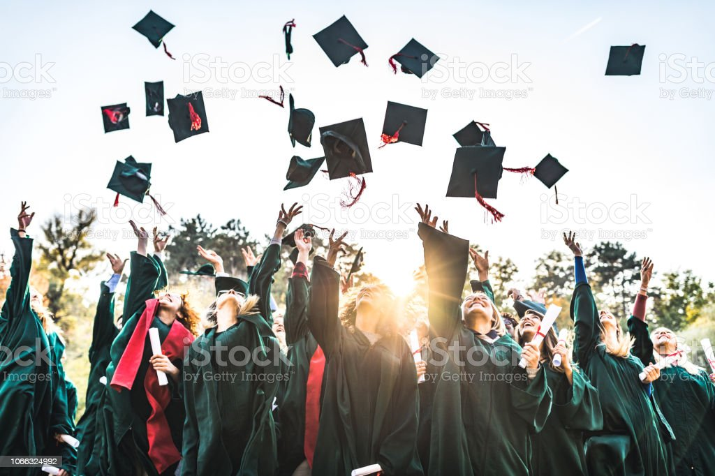 Graduation day! Large group of happy college students celebrating their graduation day outdoors while throwing their caps up in the air. Achievement Stock Photo