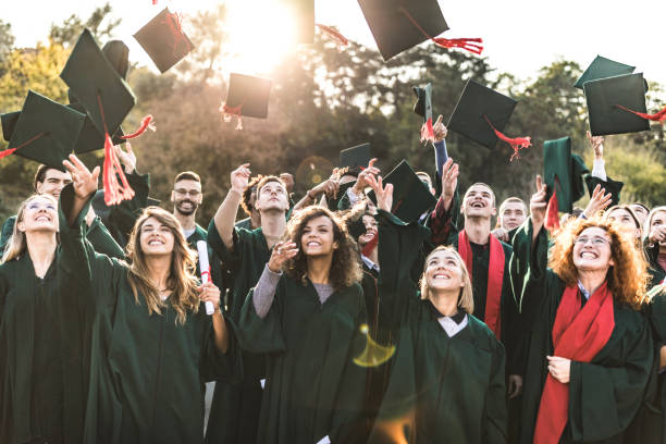 Graduation day! Large group of happy college students celebrating their graduation day outdoors while throwing their caps up in the air. alumnus stock pictures, royalty-free photos & images