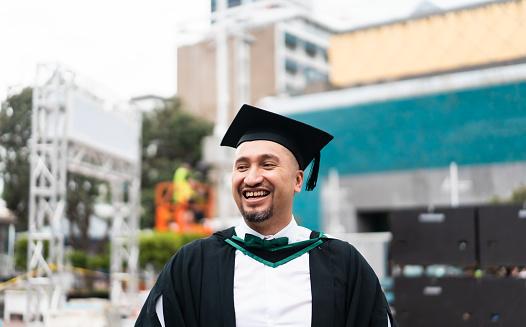 Freshly graduated man in city.