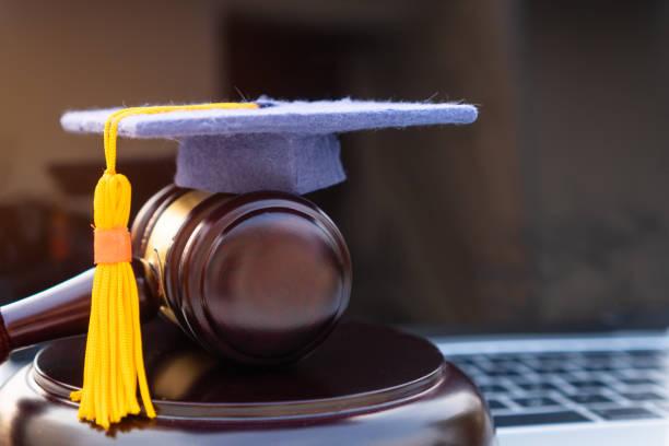 卒業証書の帽子/裁判官はコンピュータノートに与えた。学問のための大学遠隔教育における法学法証明書に関する海外大学院オンライン留学の概念 - パラリーガル ストックフォトと画像
