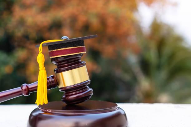 卒業証書の帽子/裁判官小槌の学校の弁護士。大学における法学の法律証明書について海外での大学院留学の概念, 自己による学習のための遠隔教育 - パラリーガル ストックフォトと画像