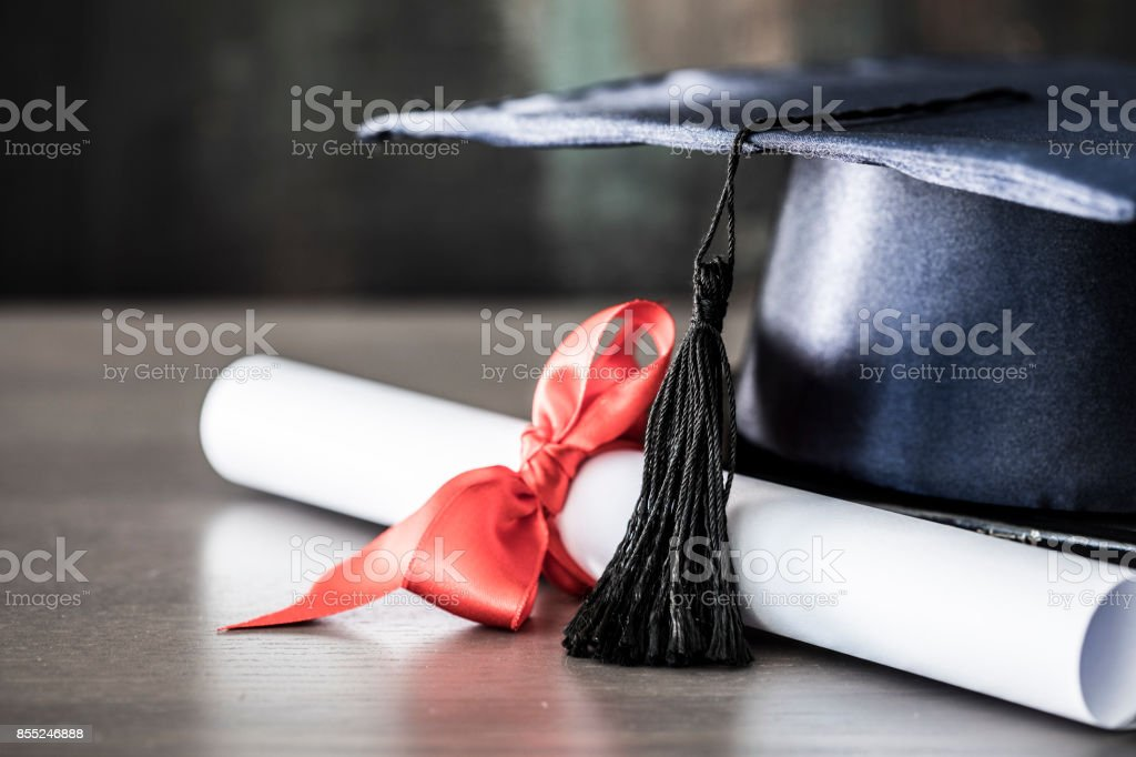 Graduation hat and diploma on table stock photo