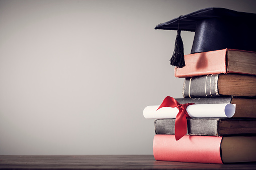 istock Graduation hat and diploma with book on table 844357338
