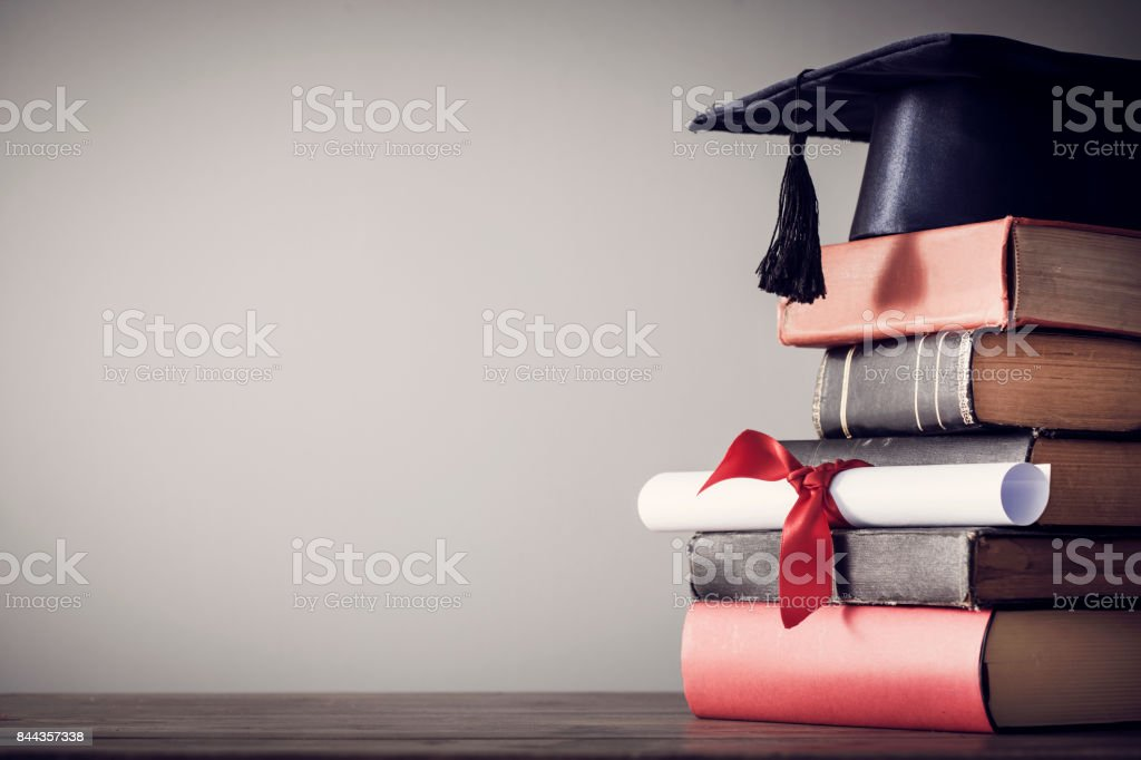 Graduation hat and diploma with book on table stock photo