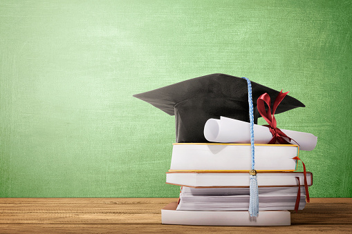 istock Graduation hat, diploma scroll and books on the wooden table 1137022077