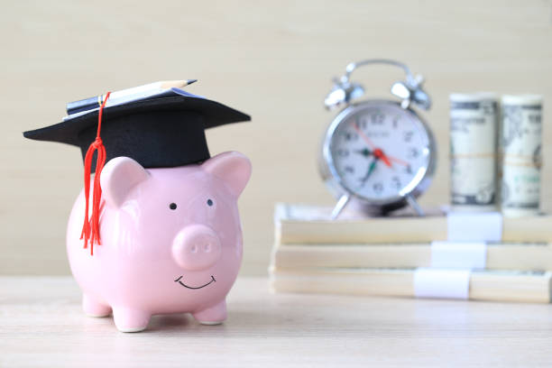 graduation hat on blue piggy bank with stack of coins money on wooden background, saving money for education concept - правописание стоковые фото и изображения