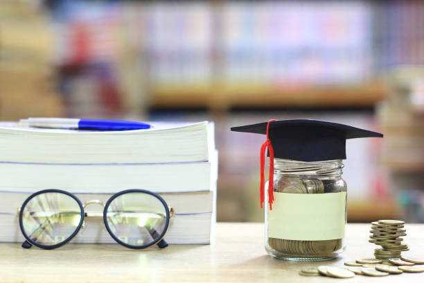 Graduation hat on the glass bottle on bookshelf in the library room background, Saving money for education concept stock photo