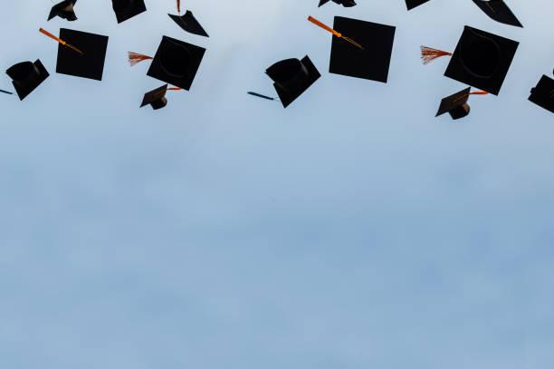 sombrero de graduación lanzado en el aire con fondo abstracto bluesky. - graduation fotografías e imágenes de stock
