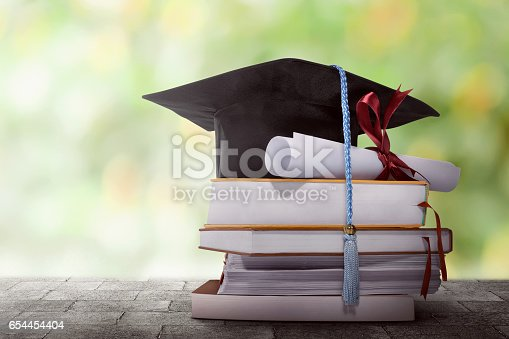 istock Graduation hat with degree paper on a stack of book 654454404