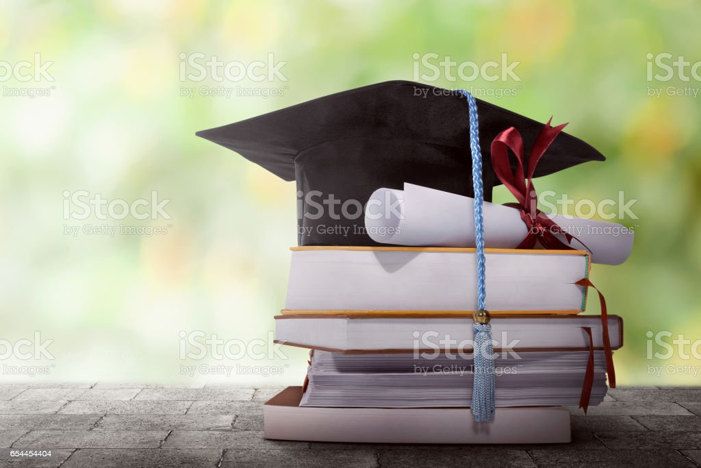 Graduation hat with degree paper on a stack of book stock photo