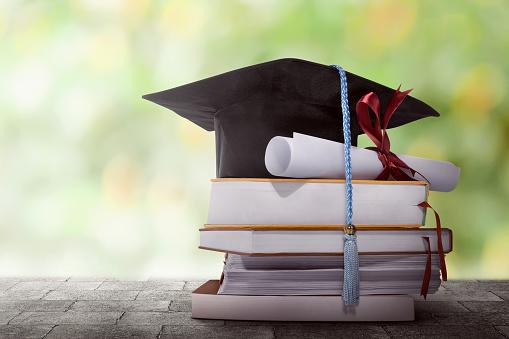 本のスタックの学位論文と卒業帽子 - お祝いのストックフォトや画像を多数ご用意