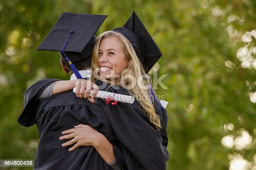 Young woman hugs a young man and smiles while they are both dressed in graduation gowns.