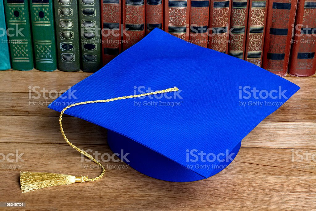 Graduation mortarboard on top of stack of books royalty-free stock photo