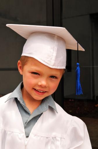 Asian Child with red book Kindergarten graduation uniform .