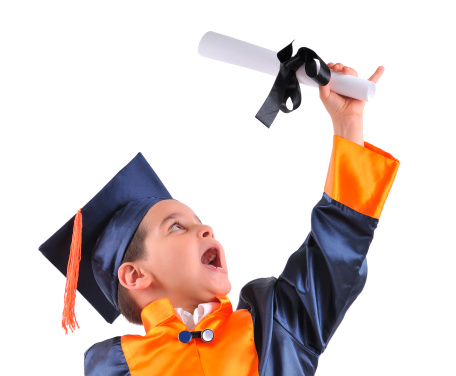 Elementary boy wearing graduation cap and gown proudly smiling at camera