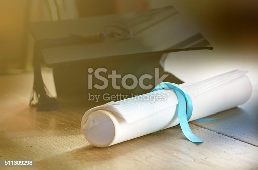 A mortarboard and graduation scroll tied with blue ribbon.