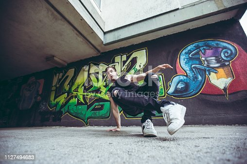 Young man is breakdancing next to graffiti covered wall