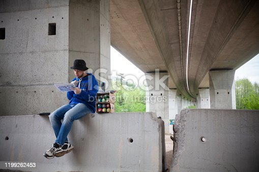 Graffiti Artist Contemplating on Graffiti Ideas Under a Highway Bridge.