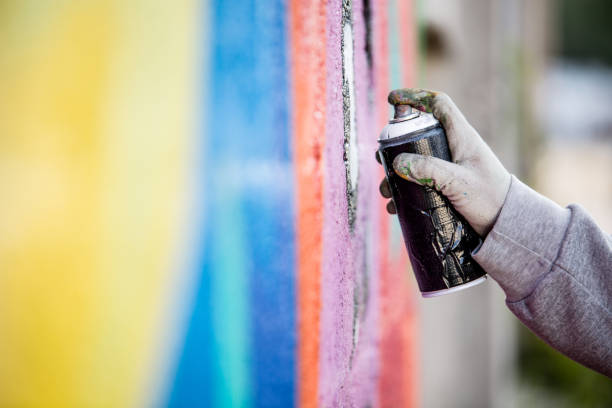 Graffiti Artist Drawing Graffiti on Wall stock photo