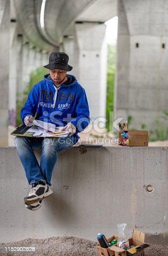 Graffiti Artist Drawing Sketch Under Highway Bridge.
