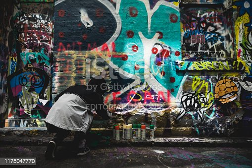 488380038 istock photo Graffiti artist painting the wall on Hosier Lane on November 10, 2018. 1175047770