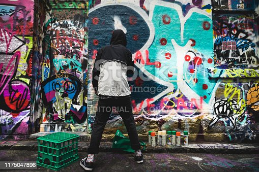 488380038 istock photo Graffiti artist painting the wall on Hosier Lane on November 10, 2018. 1175047896