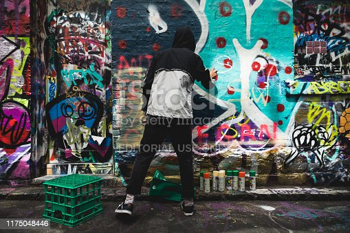 488380038 istock photo Graffiti artist painting the wall on Hosier Lane on November 10, 2018. 1175048446